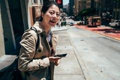 Position asiatique d'étudiante sur la rue de ville photos stock