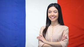 Position asiatique gaie de fille avec des mains croisées sur le fond français de drapeau clips vidéos