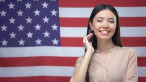 Position asiatique positive de femme sur le fond de drapeau des Etats-Unis, Jour de la Déclaration d'Indépendance clips vidéos
