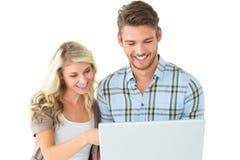 Position attrayante de couples et ordinateur portable d'utilisation Photographie stock libre de droits