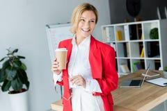 position attrayante de femme d'affaires avec du café dans la tasse de papier photo stock