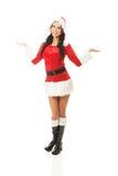Position attrayante de femme de Santa, participation quelque chose invisible des deux mains Images libres de droits