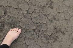 Position aux pieds nus sur le sol sec Images stock