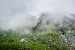 Position blanche de maison d'isolement dans le bas pré herbeux vert près des montagnes rocheuses magnifiques couvertes en brouill photographie stock libre de droits