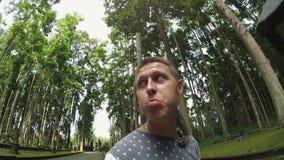 Position caucasienne de jeune homme en parc avec le singe gris se reposant sur ses épaules clips vidéos