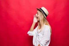 Position criarde de jeune femme d'isolement au-dessus du fond rouge photo stock