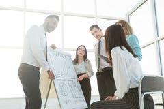 Position d'équipe d'affaires à côté de flipchart et discussion de leurs idées photos stock