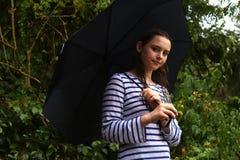 Position d'adolescente sous un parapluie sous la pluie photo stock