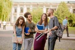 Position d'amis d'université, riant dans le campus Image stock