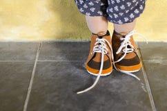 Position d'enfant en bas âge tout en portant les chaussures brunes Image libre de droits