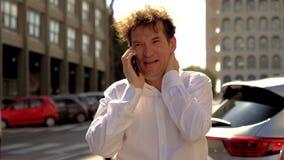 Position d'homme d'affaires dans la rue parlant au téléphone banque de vidéos