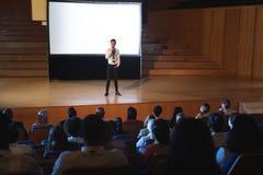 Position d'homme d'affaires et présentation de donner dans l'amphithéâtre photos stock