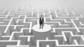 Position d'homme d'affaires sur le dessus d'un labyrinthe photo stock