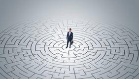 Position d'homme d'affaires ? un milieu d'un labyrinthe photographie stock libre de droits