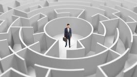 Position d'homme d'affaires ? un milieu d'un labyrinthe rond photographie stock