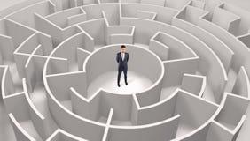 Position d'homme d'affaires ? un milieu d'un labyrinthe rond image stock