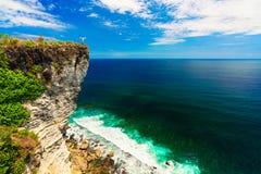 Position d'homme avec les mains augmentées sur la falaise avec la vue d'océan stupéfiant et de ciel nuageux photo stock