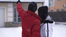 Position d'homme et de femme dans l'arrière-cour d'hiver Les points d'homme, fille l'étreint étroitement  Les couples heureux ont clips vidéos