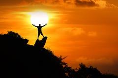 Position d'homme sur le dessus de la montagne regardant le coucher du soleil rouge de ciel image libre de droits