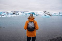 Position d'homme sur une glace dans un jokulsarlon Islande de lagune de glacier pendant un beau jour ensoleillé image stock