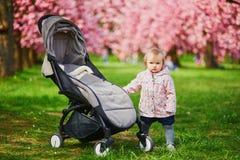 Position d'un an de fille à côté de sa poussette en parc photos stock