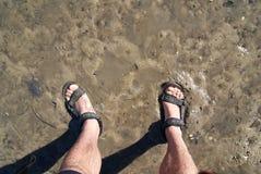 Position dans la marée basse boueuse avec des shorts et des sandales photographie stock libre de droits