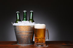 Position de bière avec la tasse sur le bois Photo stock