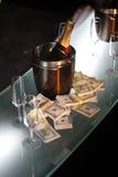 Position de champagne à côté d'argent comptant Photos stock
