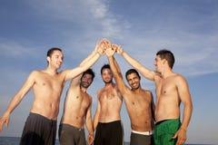 Position de cinq hommes en cercle mettant des mains dessus Images libres de droits