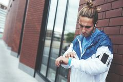 Position de coureur sur la rue près du mur de briques et de vérifier le temps de séance d'entraînement, le brassard avec le télép photographie stock libre de droits