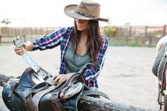 Position de cow-girl de femme et selle de préparation pour le cheval d'équitation Image stock