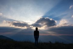 Position de femme et coucher du soleil de observation avec le Mountain View le soir photo libre de droits