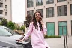 Position de femme près de voiture et appeler par le téléphone photo stock