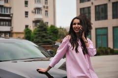Position de femme près de voiture et appeler par le téléphone images stock