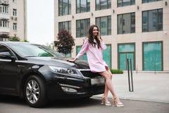 Position de femme près de voiture et appeler par le téléphone photographie stock libre de droits