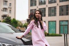 Position de femme près de voiture et appeler par le téléphone photos libres de droits