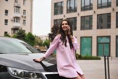Position de femme près de voiture et appeler par le téléphone photos stock