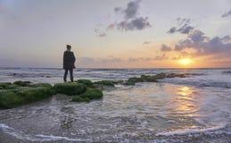 Position de femme sur des roches de mer observant le coucher du soleil photographie stock libre de droits