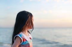 Position de fille de petit enfant de vue de côté de portrait sur la plage à la lumière de coucher du soleil avec regarder la mer images libres de droits