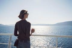 Position de fille de voyageur sur le ferry-boat, regardant la mer et tenant une tasse de café, un voyage et un concept actif de m image libre de droits