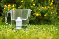 Position de filtre d'eau sur l'herbe verte dans le jardin d'été avec des fleurs sur le fond photos libres de droits