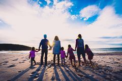 Position de groupe de famille et d'amis sur la plage tenant des mains image stock
