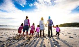 Position de groupe de famille et d'amis sur la plage tenant des mains photos libres de droits