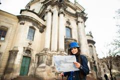 Position de jeune femme pr?s de l'?glise dans la vieille ville Lviv, et les prises une carte ? disposition l'ukraine photo stock
