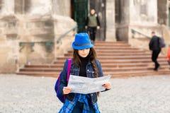 Position de jeune femme pr?s de l'?glise dans la vieille ville Lviv, et les prises une carte ? disposition l'ukraine photographie stock