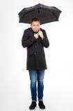 Position de jeune homme et froid d'une manière amusante de sentiment sous le parapluie Photos stock
