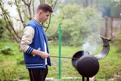 Position de jeune homme près de gril de barbecue Inflammation du feu en plein air pique-nique d'?t? en nature image libre de droits