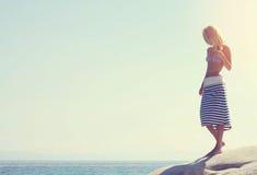 Position de marche de femmes sur la côte en pierre, plage, appréciant des vacances et des vacances, belle femme prenant un bain d Photographie stock libre de droits