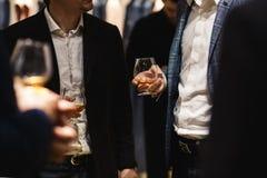 Position de personnes causant à un dîner d'affaires tenant l'échantillon en verre de whiskey et de vin et la nourriture degustati image stock