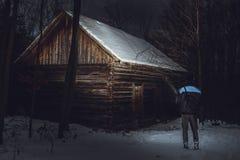 Position de photographe d'homme devant le cottage abadoned et rampant dans la forêt en hiver L'homme sur l'expédition shinning av images stock